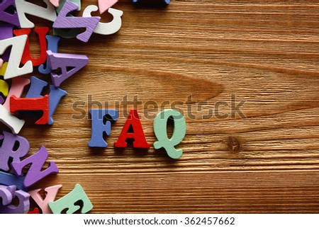 FAQ- words  made from multicolored   letters on wooden  background