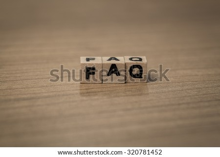faq written in wooden cubes on a desk - stock photo