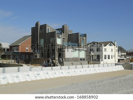 FAR ROCKAWAY, NY - OCTOBER 22: Damaged beach house in devastated area one year after Hurricane Sandy on October 22, 2013 in Far Rockaway, NY. Notice protective barrier build to prevent flooding