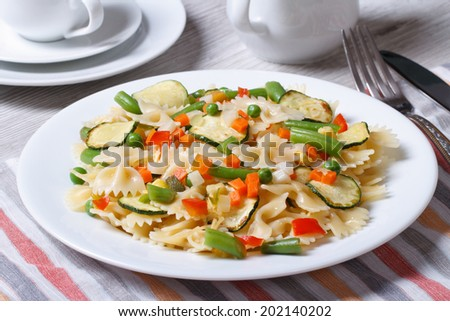 Farfalle pasta with slices of vegetables, cheese closeup on a white plate on the table horizontal   - stock photo