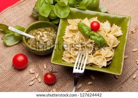 Farfalle With Pesto - Overhead shot of Italian pasta garnished with pesto sauce. - stock photo