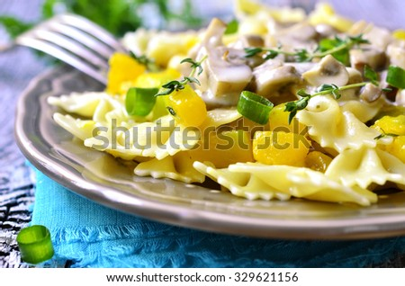 Farfalle with pumpkin in mushroom sauce on rustic wooden table.