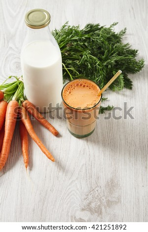 Farm carrot harvest lying near milk bottle and glass filled with mix natural fresh juice and milk with golden drinking straw in it,for breakfast. Isolated top view on wooden table in cafe - stock photo
