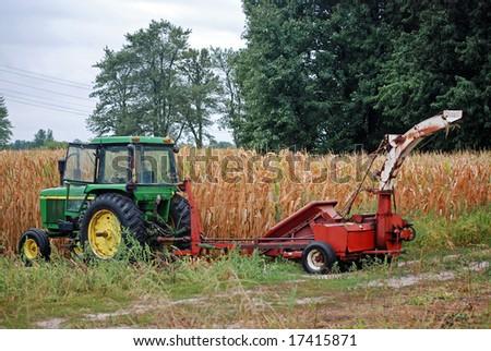 farm equipment in cornfield - stock photo