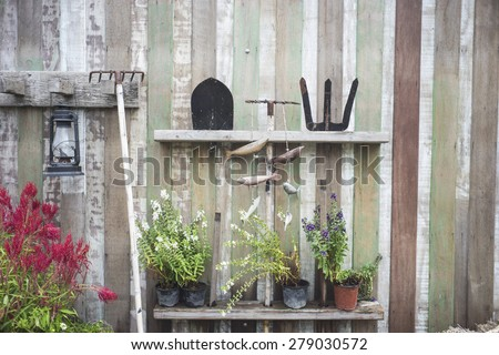 farm equipment on wooden wall with plants - stock photo