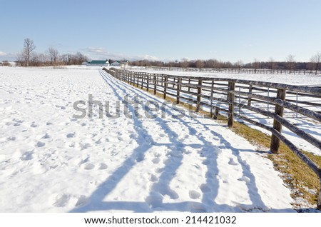 Farm fence and lines of shadows in winter time - stock photo