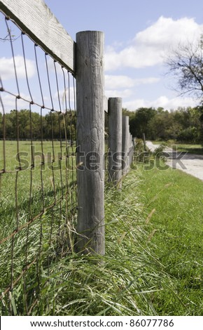 Farm fence by dirt road in American Midwest (shallow depth of field; focus on post in foreground) - stock photo