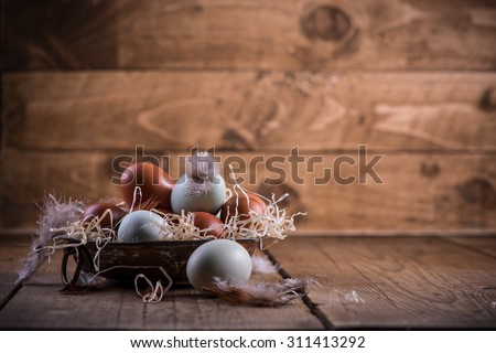 Farm fresh free range eggs in rustic bowl, on wooden table - stock photo