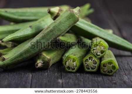 Farm fresh raw okra on wooden rustic table - stock photo