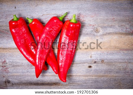 Farm fresh whole red hot cayenne chili peppers for a spicy food seasoning lying on an old wooden rustic kitchen table with copyspace, view from above - stock photo