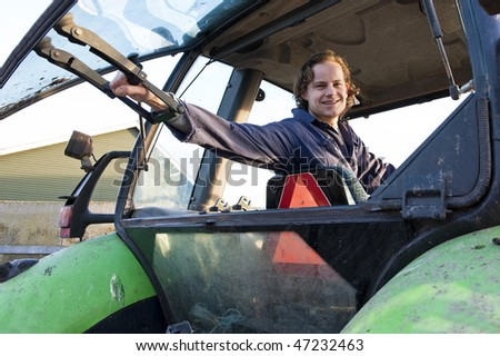 Farm hand looking out the rear window of a tractor, hodling the lever - stock photo