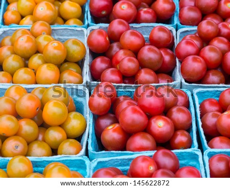 Farm market display of tomatoes of varying colors.