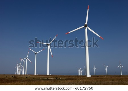 Farm of wind turbines against a blue sky - stock photo