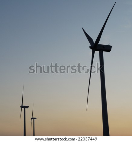 farm of windturbines on sunset
