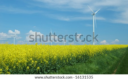 farm of winturbines close to rapeseed field France - stock photo