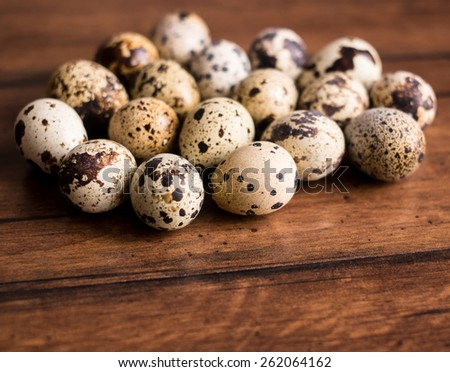 Farm quail eggs on the wooden rustic surface, selective focus - stock photo