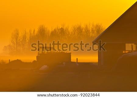 Farm scene during orange sunset - stock photo