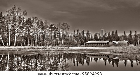 farm showing the horse barn by the lake - stock photo