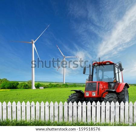 Farm. The green field and a tractor behind a fence - stock photo