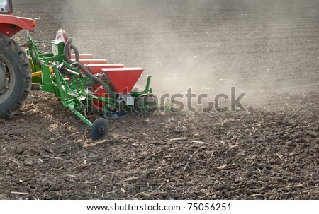 farm tractor and seeder planting crops on a field - stock photo