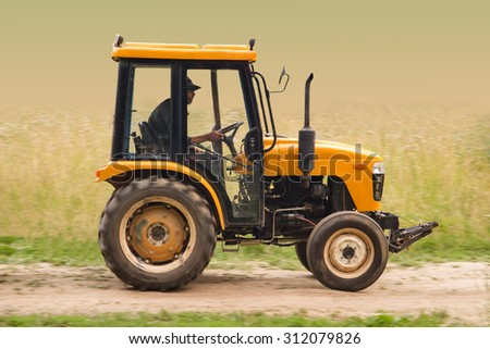 Farm tractor goes on road - stock photo