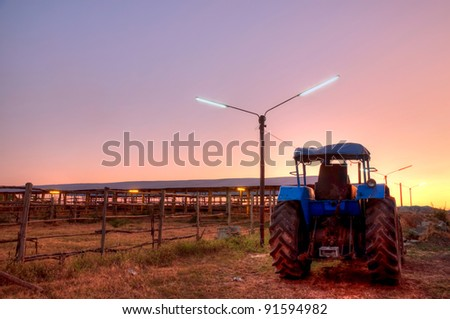 farm tractor in the sunset sky background - stock photo