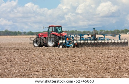 Farm tractor planting corn in a field - stock photo