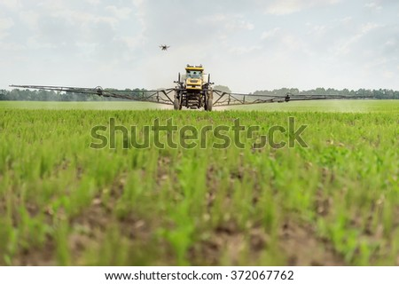 Farm tractor sprays a field toxins from pests, unmanned helicopter takes off process - stock photo
