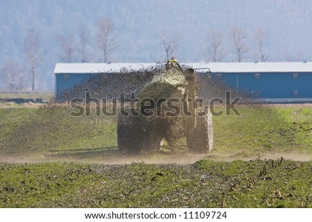 Farm tractor spreading manure before spring seeding - stock photo