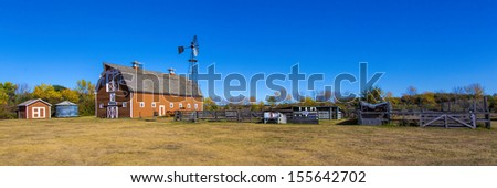 Farm yard with a red barn, wind mill and other buildings. - stock photo