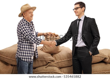 Farmer and a businessman shaking hands in front of a pile of burlap sacks filled with potatoes isolated on white background