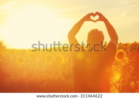Farmer at sunset in the field, heart shape hands. - stock photo