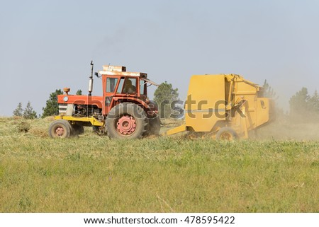Farmer bailing hay into round bales after harvesting
