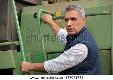 Farmer climbing into a tractor - stock photo