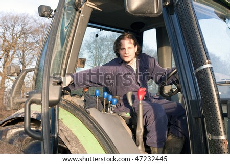 Farmer closing the door of a tractor - stock photo