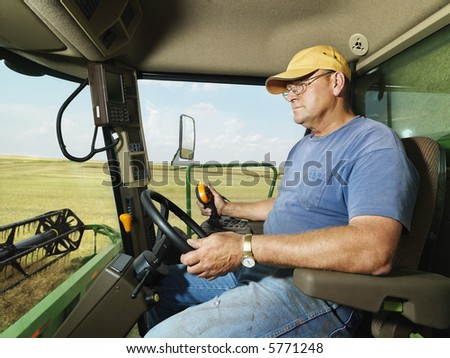 Farmer driving combine and harvesting crop. - stock photo