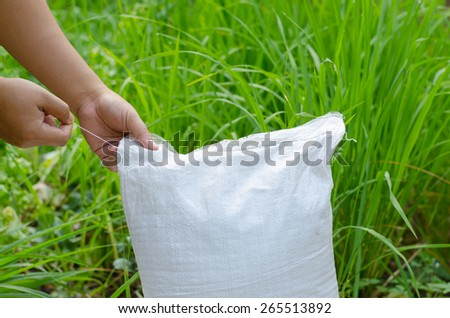Farmer hand unpacking plant fertilizer bag - stock photo