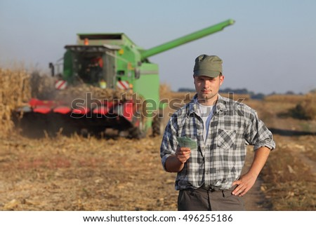 Farmer holding Euro banknote with combine harvester in background, corn harvest concept