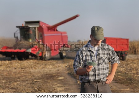 Farmer holding Euro banknote with combine harvester in background, serious face, corn harvest concept