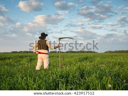 Farmer in a hat  and with a scythe on green field - stock photo