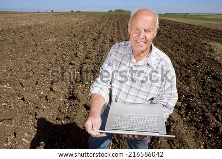 Farmer in ploughed farm field using laptop - stock photo