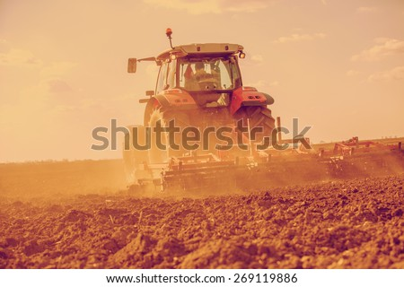 Farmer in tractor preparing land with seedbed cultivator. Filtered image. - stock photo