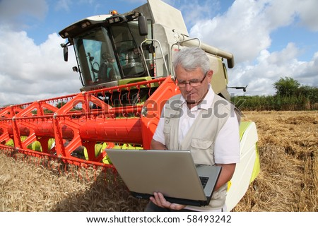 Farmer in wheat field with harvester - stock photo