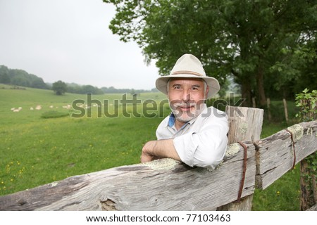 Farmer leaning on farmland fence - stock photo