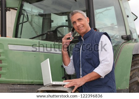 farmer near a tractor with computer - stock photo