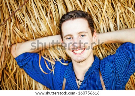 farmer near the hay stack (soft focus on his eyes) - stock photo