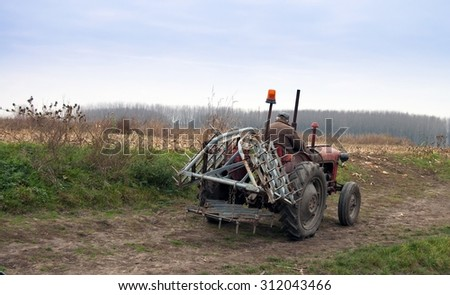 Farmer on old tractor cramps stubble on his field in Serbia. Preparing the country for the autumn plowing. - stock photo