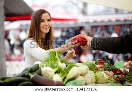 Farmer passing young woman a red pepper at the market - stock photo