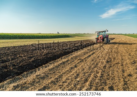 Farmer plowing stubble field with red tractor - stock photo