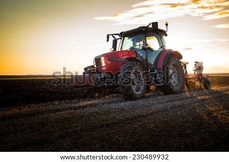 Farmer plowing stubble field with red tractor at sunset - stock photo